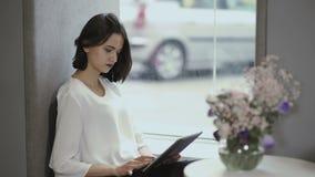 Compressa di uso della ragazza che si siede sul davanzale della finestra archivi video