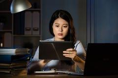 Compressa digitale di affari di uso asiatico della donna che funziona fuori orario fotografia stock libera da diritti