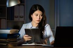 Compressa digitale di affari di uso asiatico della donna che funziona fuori orario immagine stock libera da diritti
