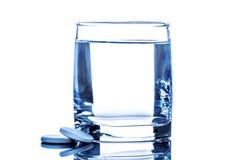 Compressa due vicino a bicchiere d'acqua Fotografia Stock Libera da Diritti