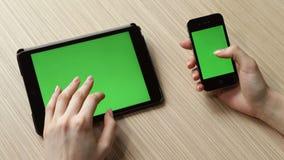 Compressa e smartphone di Digital con lo schermo verde sulla tavola stock footage