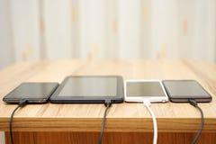 Compressa e telefoni cellulari del computer che fanno pagare sullo scrittorio domestico immagine stock