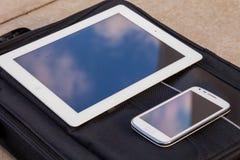 Compressa e telefono cellulare su una borsa alla moda Copi lo spazio outdo Fotografia Stock
