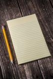 Compressa gialla sullo scrittorio d'annata fotografia stock