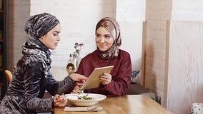 Compressa musulmana graziosa di uso della donna due in caffè video d archivio