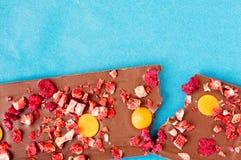 Compressa rotta del cioccolato al latte dell'arancia, della fragola e del lampone Fotografie Stock Libere da Diritti