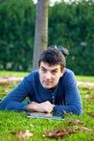 Compressa sorridente bella della lettura dell'uomo in parco in autunno Fotografia Stock Libera da Diritti