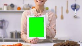 Compressa sorridente della tenuta della casalinga con lo schermo verde, app di consegna dei prodotti stock footage