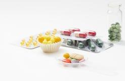 Compresse, capsule e vitamine in bolle isolate Fotografia Stock