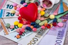 Compresse colourful disperse e cuore rosso sulle euro fatture, fotografia stock libera da diritti