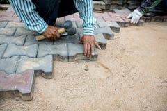 Compresse de marteau d'utilisation de travailleur pavant des blocs à fortement avec le plancher pour accumuler le passage couvert image libre de droits