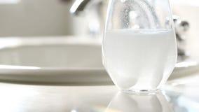 Compresse effervescenti della medicina che sono cadute nel bicchiere d'acqua archivi video