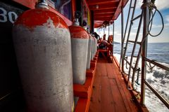 Compressed air tanks preparing for diving trip. On wooden boat royalty free stock photography