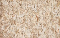 Compressed light brown wooden plywood texture. Fiberboard. Compressed light brown wooden plywood texture. Close up surface of pressed wood-shaving plate. Old royalty free stock photo