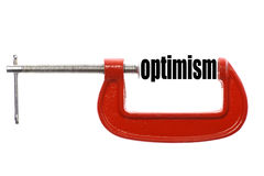 Compressed optimism concept. The word optimism is compressed with a vice Stock Photo