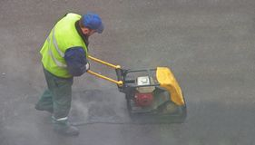 Compressing asphalt. Road mender at work; hard work, power, blue-collar concept royalty free stock images