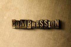 COMPRESSION - close-up of grungy vintage typeset word on metal backdrop Stock Image