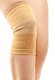 Compression knee brace. Closeup of a woman legs with one compression knee brace; isolated on white royalty free stock image