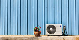 Compressor air-conditioner and Flower Pot on zinc wall Royalty Free Stock Photography