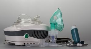 Compressor inhaler with mask, small pocket device for asthmatics and phonendoscope on gray. Background Royalty Free Stock Photography
