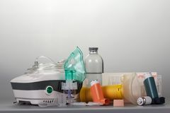Compressor and portable inhalers, replaceable dispenser, ampoules and baby mask, on grey. Background Royalty Free Stock Photos