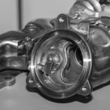 Compressor for turbo car internal combustion engine. New turbocharger compressor isolated on gray background stock photo