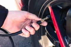 Compressore d'aria di collegamento dell'uomo alle gomme di automobile Fotografia Stock