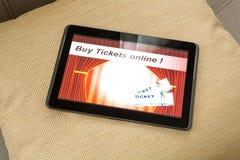 Compri i biglietti del cinema online con un PC della compressa Fotografie Stock