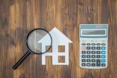 Compri i calcoli di ipoteca della casa, calcolatore con la lente immagini stock libere da diritti
