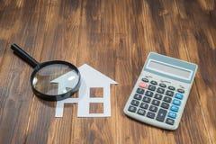 Compri i calcoli di ipoteca della casa, calcolatore con la lente Fotografia Stock