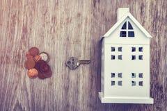 Compri il concetto dell'alloggio Casa, chiave e monete dei soldi per comprare casa Immagine Stock