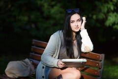 Comprimé électronique d'étudiante se reposant sur un banc image stock