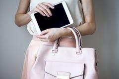 Comprimé électronique de Digital sur des mains du ` un s de femme Sac à main rose-clair en cuir, style élégant d'été Photos stock