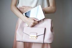 Comprimé électronique de Digital sur des mains du ` un s de femme Sac à main rose-clair en cuir, style élégant d'été Photographie stock