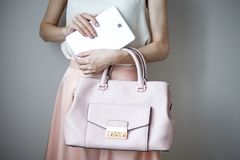 Comprimé électronique de Digital sur des mains du ` un s de femme Sac à main rose-clair en cuir, style élégant d'été Image stock