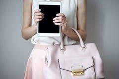 Comprimé électronique de Digital sur des mains du ` un s de femme Sac à main rose-clair en cuir, style élégant d'été Photos libres de droits