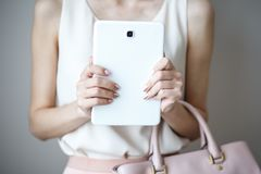 Comprimé électronique de Digital sur des mains du ` un s de femme Sac à main rose-clair en cuir, style élégant d'été Images stock