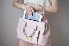 Comprimé électronique de Digital sur des mains du ` un s de femme Sac à main rose-clair en cuir, style élégant d'été Images libres de droits
