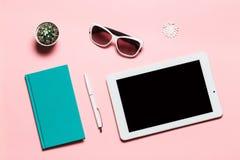 Comprimé blanc, journal intime vert-bleu, stylo, verres, flocon de neige et cactus sur le fond rose Composition plate en configur Photos libres de droits