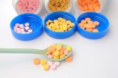 Comprimé coloré de médecine sur la cuillère et la bouteille ouverte de médecine Photos stock
