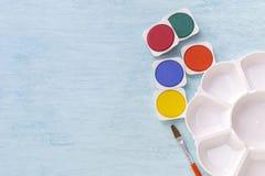 Comprimé d'aquarelle et palette colorés de peinture avec l'espace sur le fond bleu de table photographie stock libre de droits
