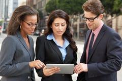 Comprimé d'And Businesswomen Using Digital d'homme d'affaires dehors photographie stock