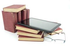 Comprimé d'EBook avec la pile de vieux livres et verres imprimés Photos stock