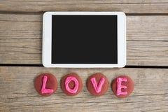 Comprimé de Digital avec des biscuits affichant le message d'amour sur la surface en bois Image libre de droits