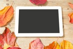Comprimé de Digital et feuilles d'automne sur le fond en bois Photo stock