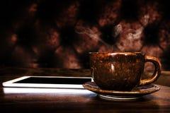 Comprimé de Digital et tasse de café sur la table en bois photos stock