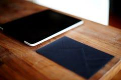 Comprimé de Digital se trouvant sur la table à côté de lui enveloppe noire élégante Image stock