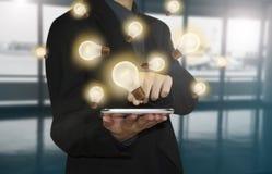 Comprimé de presse de main d'affaires avec l'ampoule, concept de nouvelles idées photo libre de droits
