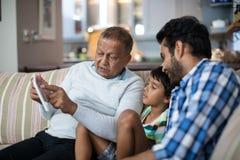 Comprimé de représentation première génération au petit-fils s'asseyant avec le père à la maison Photo libre de droits