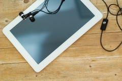 Comprimé et écouteurs de Digital sur le fond en bois Image stock